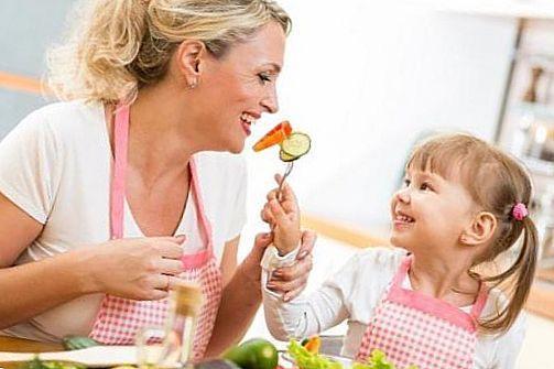мама і дочка їдять овочі